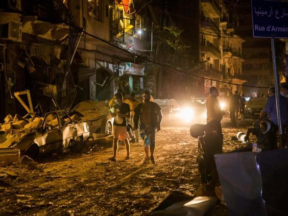 People walk on a street covered in debris (Getty Images)