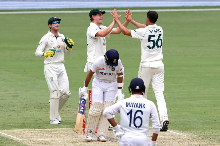 Australia's paceman Mitchell Starc (R) celebrates the wicket of India's captain Ajinkya Rahane (C) with teammates on day three of the fourth cricket Test match between Australia and India at The Gabba in Brisbane on January 17, 2021.