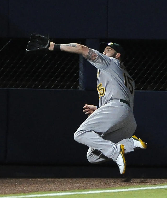 Oakland Athletics left fielder Jonny Gomes jumps to field the pop out in foul territory by Atlanta Braves' Jason Heyward during the first inning of a baseball game Sunday, Aug. 17, 2014, in Atlanta. (AP Photo/David Tulis)
