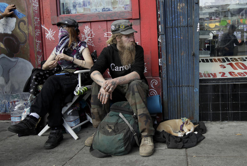 In this Oct. 1, 2018 photo, Stormy Nichole Day, left, sits on a sidewalk on Haight Street with Nord (last name not given) and his dog Hobo while interviewed about being homeless in San Francisco. A measure on San Francisco's Nov. 6 ballot would levy an extra tax on hundreds of the city's wealthiest companies to raise $300 million for homelessness and mental health services. It's the latest battle between big business and social services advocates who say that companies such as Amazon, Google and Salesforce can afford to help solve severe inequities caused by business success. (AP Photo/Jeff Chiu)