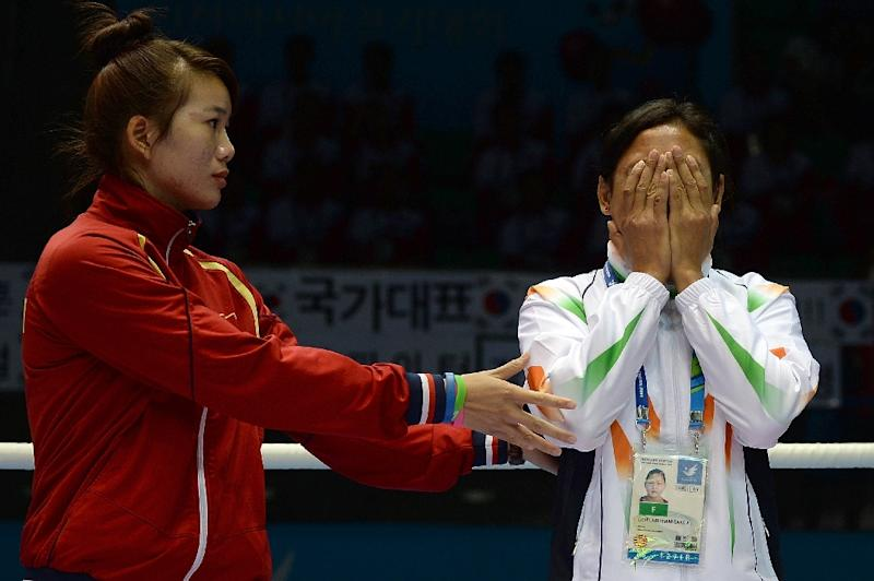 India's Sarita Devi is distraught on the 2014 Asian Games medal podium after refusing her bronze medal as Vietnam's Luu Thi Duyen tries touchingly to console her (AFP Photo/INDRANIL MUKHERJEE)
