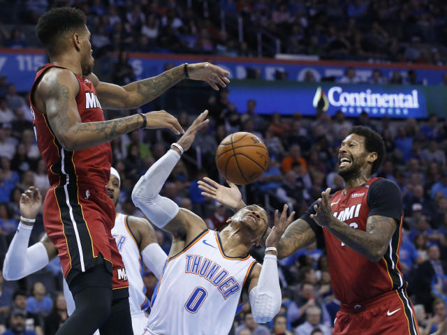 Miami Heat guard Rodney McGruder, left, Oklahoma City Thunder guard Russell Westbrook (0) and forward James Johnson, right, reach for a rebound during the first half of an NBA basketball game in Oklahoma City, Friday, March 23, 2018. (AP Photo/Sue Ogrocki)