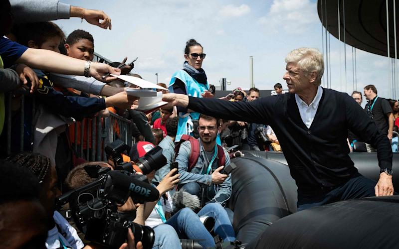 Arsene Wenger signs autographs after a football match for a children's association at the Stade de France this week - AFP
