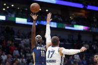 New Orleans Pelicans guard Jrue Holiday (11) shoots over Memphis Grizzlies center Jonas Valanciunas (17) during the first half of an NBA basketball game in New Orleans, Friday, Jan. 31, 2020. (AP Photo/Gerald Herbert)