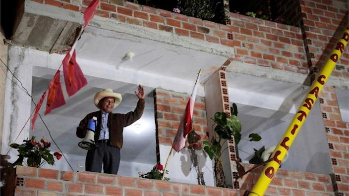 Pedro Castillo waves to supporters in the town of Tacabamba, as he waits for votes to be counted