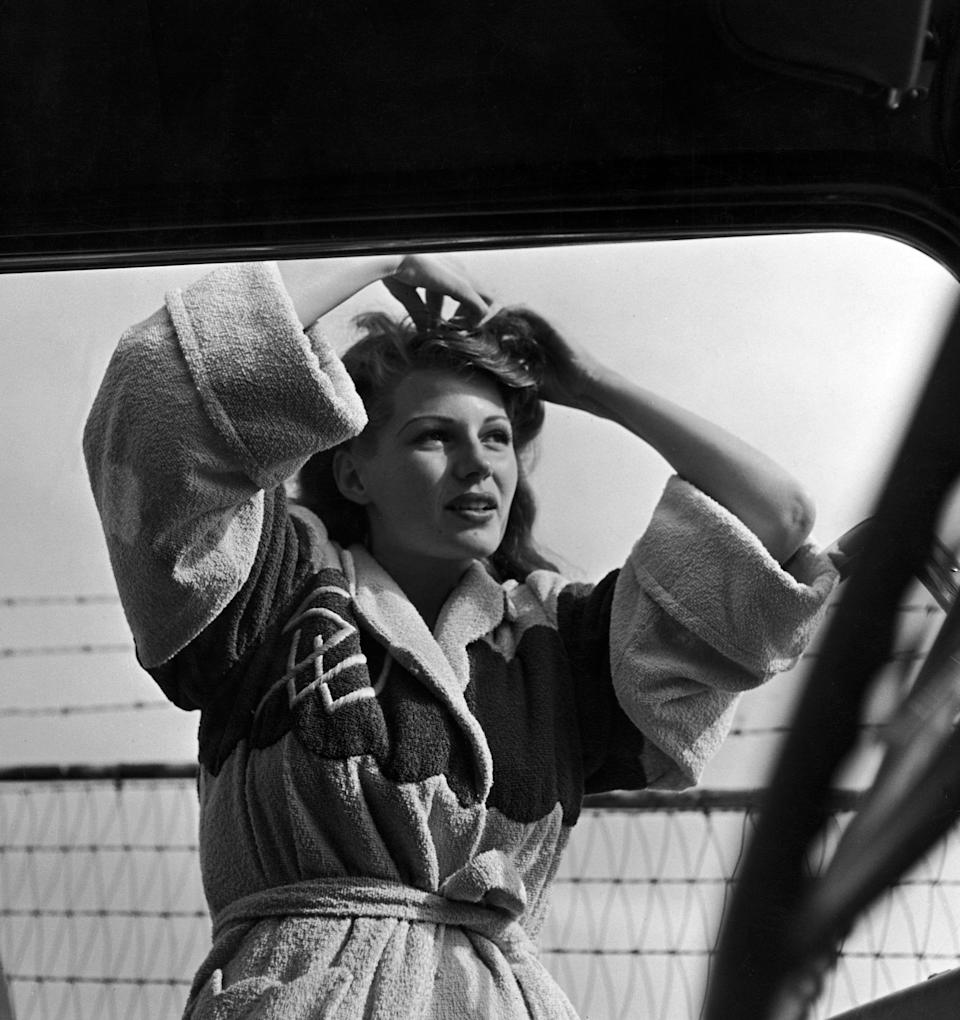 Hayworth wears a bathrobe over her swimsuit as she pins up her hair while standing next to parked car at the beach in this undated photo.