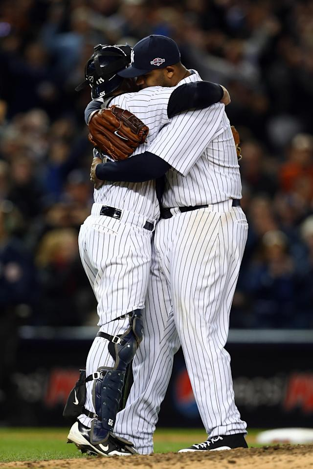 NEW YORK, NY - OCTOBER 12: CC Sabathia #52 and Russell Martin #55 of the New York Yankees celebrate after defeating the Baltimore Orioles by a score of 3-1 to win Game Five of the American League Division Series at Yankee Stadium on October 12, 2012 in New York, New York. (Photo by Elsa/Getty Images)