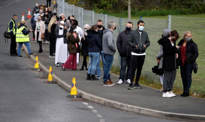 People line up outside a mobile vaccination centre, in Bolton