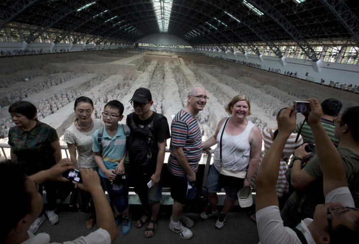 In this Tuesday, July 30, 2013 photo, foreign and local tourists have their souvenir photos taken near a display of the unearthed terracotta warriors as they visiting the excavation site inside the No.1 pit of the Museum of Qin Terracotta Warriors and Horses in Xi'an, in central China's Shaanxi province. China, one of the most visited countries in the world, has seen sharply fewer tourists this year — with worsening air pollution partly to blame. (AP Photo/Andy Wong)