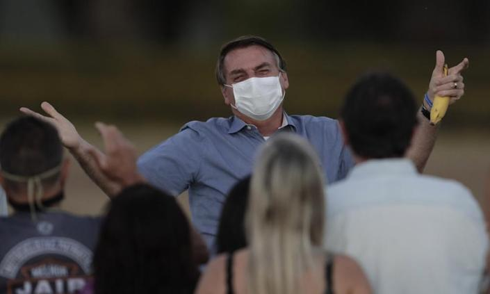President Jair Bolsonaro greets supporters outside his official residence the Alvorada Palace, in Brasília, on 24, after he tested positive for coronavirus earlier that month.