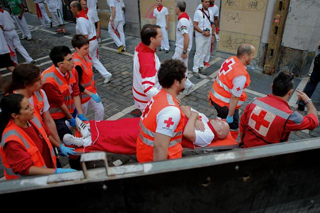 PAMPLONA, SPAIN - JULY 08: Medical services carry a man after Dolores Aguirre's ranch fighting bulls passed along Curva Estafeta during the third day of the San Fermin Running Of The Bulls festival, on July 8, 2013 in Pamplona, Spain. The annual Fiesta de San Fermin, made famous by the 1926 novel of US writer Ernest Hemmingway 'The Sun Also Rises', involves the running of the bulls through the historic heart of Pamplona for nine days from July 6-14. (Photo by Pablo Blazquez Dominguez/Getty Images)