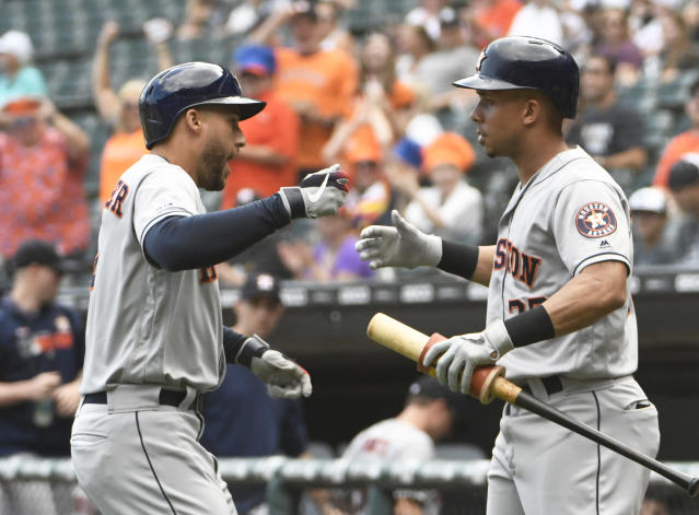 Houston Astros' George Springer, left, is greeted by Michael Brantley, right, after hitting a home run against the Chicago White Sox during the first inning of game one of a baseball doubleheader, Tuesday, Aug. 13, 2019, in Chicago. (AP Photo/David Banks)