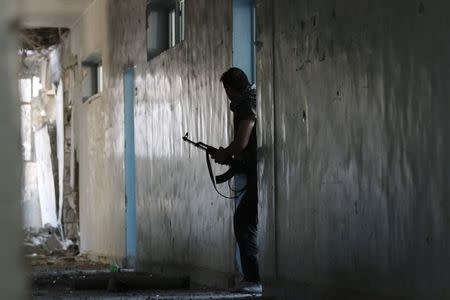 A Free Syrian Army fighter walks with his weapon inside a damaged building on the frontline of Aleppo's Al-Ezaa neighbourhood