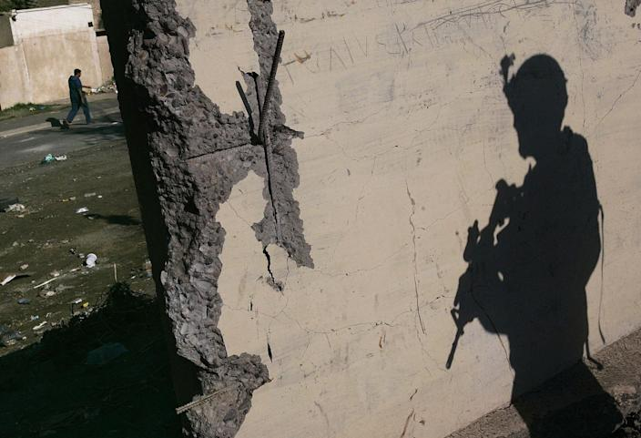 <p>A US Army soldier with Task Force Dagger stands watch while a man passes by in the distance on December 1, 2006 in the Hurriyah neighborhood of Bagdhad, Iraq. Hurriyah has been the site of violent incidents in recent weeks, including alleged sectarian mosque burnings and the killing of an U.S. Army colonel by a roadside bomb, one of the highest ranking American deaths in the Iraq war. (Photo by Chris Hondros/Getty Images) </p>