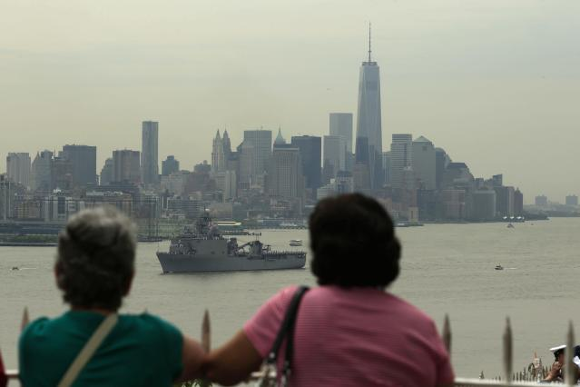People stand in Weehawken, New Jersey, to look at the USS Oak Hill, a Harpers Ferry-class dock landing ship of the United States Navy, as it arrives in New York Harbor for Fleet Week in New York May 21, 2014. REUTERS/Eduardo Munoz (UNITED STATES - Tags: MILITARY MARITIME)