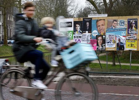 A man and child cycle past an election poster billboard the day before a general election in Utrecht in the Netherlands
