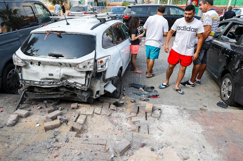 Israeli men stand next to a car that was damaged after a rocket fired by militants from the Gaza Strip fell in the southern Israeli town of Sderot on August 9, 2018 (AFP Photo/JACK GUEZ)