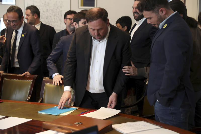 The leader of the Catalonian ERC party Oriol Junqueras, centre, prepares to sign some documents and collect his credentials alongside the ERC parliamentary spokesperson Gabriel Rufian, right, inside the Spanish parliament in Madrid, Spain, Monday May 20, 2019. The five separatist leaders on trial for Catalonia's 2017 secession attempt who were elected to the Spanish Parliament in April 28 elections have been escorted by police to pick up their official parliament credentials. The Supreme Court is allowing the five politicians to get their credentials on Monday and attend the opening session of the new Parliament on Tuesday. (J.J. Guillen/Pool Photo via AP)