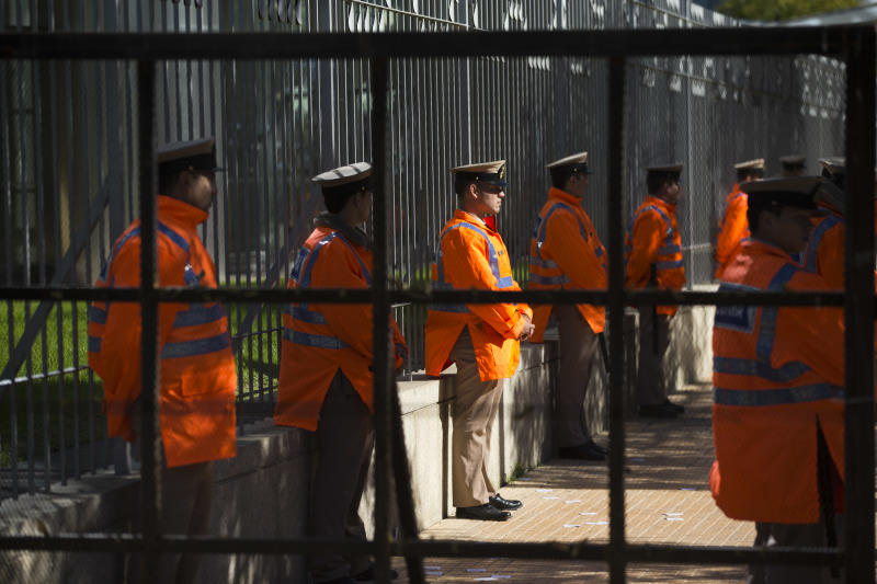 Police stand guard behind fences in front of Argentina's state-controlled YPF oil company headquarter during a protest against a deal between YPF and U.S. oil company Chevron in Buenos Aires, Argentina, Tuesday, July 16, 2013. YPF, which was expropriated in 2012 from Spain's Repsol, is finalizing the details of an agreement with Chevron which would invest in the first pilot for massive exploration for unconventional oil and gas in the Vaca Muerta region. (AP Photo/Victor R. Caivano)