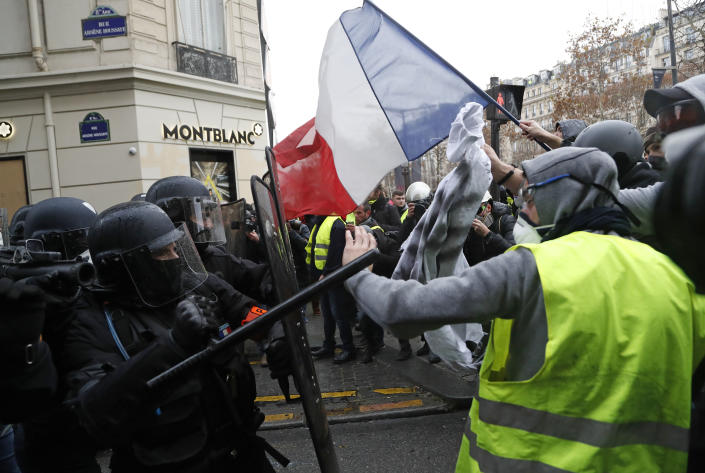 Police officers clash with demonstrators wearing yellow vests in Paris on Saturday. (Photo: Thibault Camus/AP)