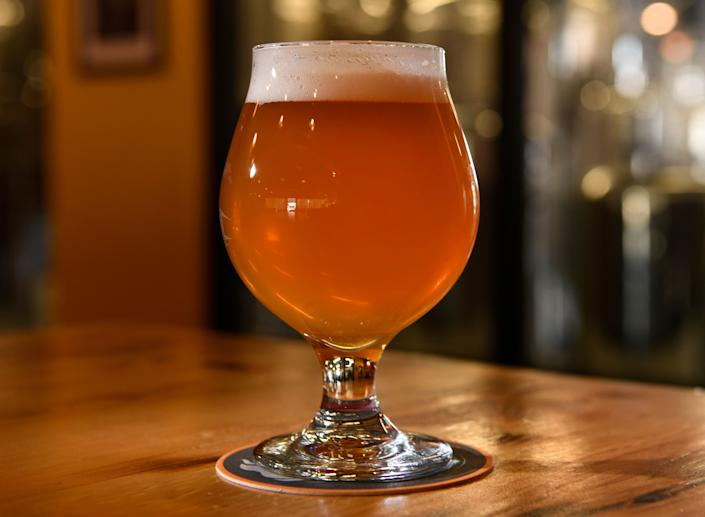 """<strong>Flavor:</strong>A strong hoppy flavor, with a slightly (or extremely) bitter taste.<br /><br /><strong>Color:</strong>Usually amber and cloudy, but IPAs come in a range of darker and lighter colors now.<br /><br /><strong>Strength: </strong>Typically <a href=""""https://www.beeradvocate.com/beer/style/150/"""" target=""""_blank"""">4.5-6 percent ABV</a>, but some brewers have tried to recreate the original IPAs with an ABV closer to 8 or 9 percent.<br /><br /><strong>Fun Fact:</strong> During the 1700s, when English troops lived in India, the typical pale ale brew most Englishmen drank would spoil before the ship reached the Indian shores. In order to prolong the beer's shelf life, <a href=""""https://www.theguardian.com/lifeandstyle/2015/jan/30/brief-history-of-ipa-india-pale-ale-empire-drinks"""" target=""""_blank"""">brewers added more hops</a>, which is a natural preservative. And that's how the hoppiest beer style was born."""