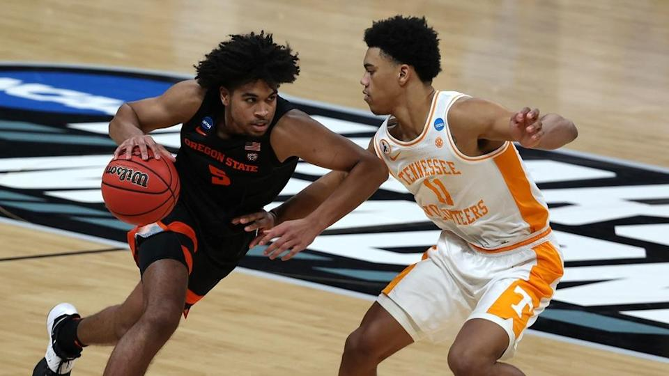 Mar 19, 2021; Indianapolis, Indiana, USA; Oregon State Beavers guard Ethan Thompson (5) dribbles the ball while defended by Tennessee Volunteers guard Jaden Springer (11) during the second half in the first round of the 2021 NCAA Tournament at Bankers Life Fieldhouse.