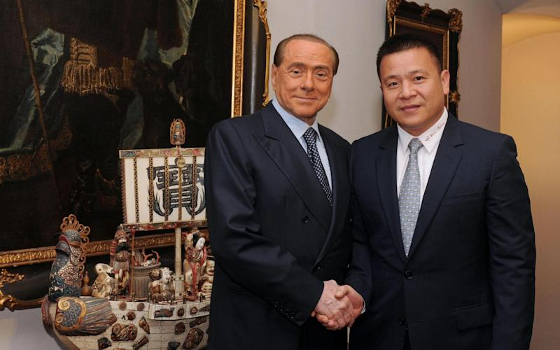 The new owner of AC Milan, Li Yonghong (R), shakes hand with former president Silvio Berlusconi - Credit: EPA