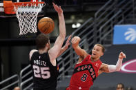 Toronto Raptors guard Malachi Flynn (8) makes a pass around San Antonio Spurs center Jakob Poeltl (25) during the second half of an NBA basketball game Wednesday, April 14, 2021, in Tampa, Fla. (AP Photo/Chris O'Meara)
