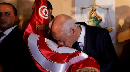Tunisian presidential candidate Kais Saied reacts after exit poll results were announced in a second round runoff of the presidential election in Tunis