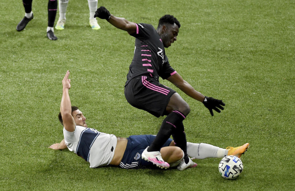 Vancouver Whitecaps forward Lucas Cavallini, left, pokes the ball away as he slides in on Seattle Sounders defender Yeimar Gomez during the second half of an MLS soccer match in Portland, Ore., Tuesday, Oct. 27, 2020. Seattle won 2-0. (AP Photo/Steve Dykes)