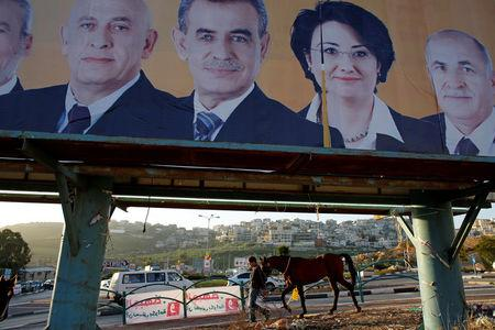 FILE PHOTO:  A man walks with a horse near a campaign poster for the National Democratic Assembly party in the Israeli-Arab city of Umm el-Fahm January 14, 2013. REUTERS/Ammar Awad/File Photo