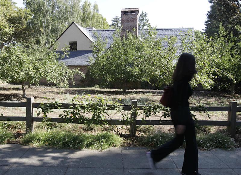 A pedestrian walks by the house of Steve Jobs in Palo Alto, Calif., Friday, Aug. 17, 2012. Kariem McFarlin, 35, was arrested on Aug. 2, 2012 and accused of breaking into the Jobs home and stealing iPods, Macs, jewelry and Jobs' wallet on July 17, 2012, investigators said. (AP Photo/Paul Sakuma)