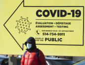 A man bundles up against the cold and wears a face mask for safety from COVID-19 as he walks past a testing clinic, Friday, Feb. 12, 2021, in Montreal. (Ryan Remiorz/The Canadian Press via AP)