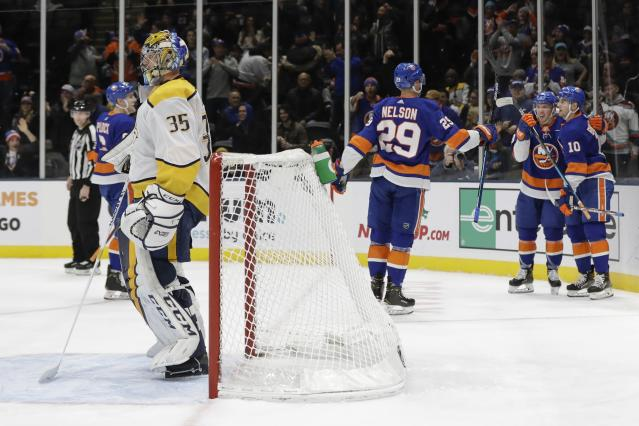 New York Islanders' Derick Brassard (10) celebrates with teammates after scoring a goal as Nashville Predators goaltender Pekka Rinne (35) reacts during the second period of an NHL hockey game Tuesday, Dec. 17, 2019, in Uniondale, N.Y. (AP Photo/Frank Franklin II)