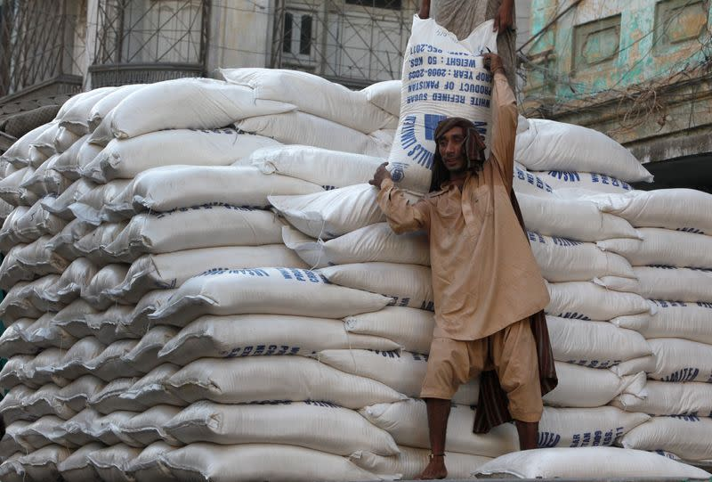 A labourer unloads bags of sugar from a delivery truck to a market in Karachi