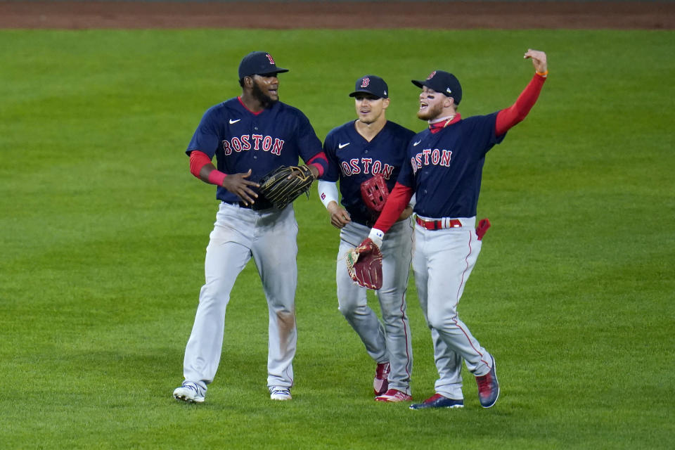 Boston Red Sox outfielders, from left, Franchy Cordero, Enrique Hernandez and Alex Verdugo react after defeating the Baltimore Orioles 6-4 in ten innings during a baseball game, Saturday, April 10, 2021, in Baltimore. (AP Photo/Julio Cortez)