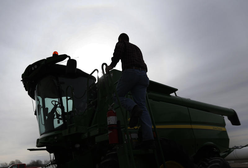 Nick Guetterman climbs into a combine on his farm near Bucyrus, Kan., Wednesday, Feb. 19, 2014. Farmers from across the nation gathered in Washington this month for their annual trek to seek action on the most important matters in American agriculture. But this time, a new issue emerged: growing unease about how the largest seed companies are gathering vast amount of data from sensors on tractors, combines and other farm equipment. The sensors measure soil conditions, seeding rates, crop yields and many other variables. (AP Photo/Orlin Wagner)