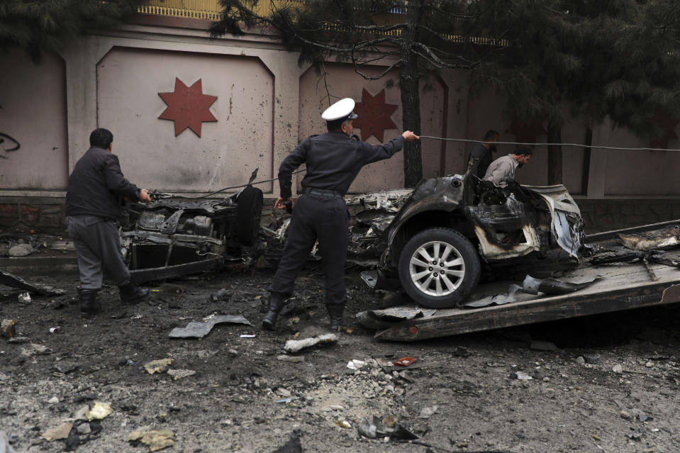 Afghan security personnel remove a damaged vehicle from the site of a bomb attack in Kabul, Afghanistan, Saturday, Feb. 20, 2021. Three separate explosions in the capital Kabul on Saturday killed and wounded numerous people an Afghan official said. (AP Photo/Rahmat Gul)