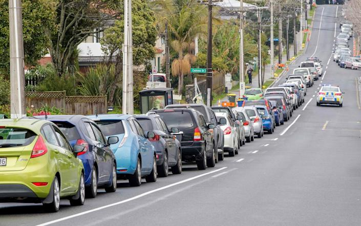 Motorists queue at a coronavirus testing centre in the suburb of Northcote in Auckland - AFP