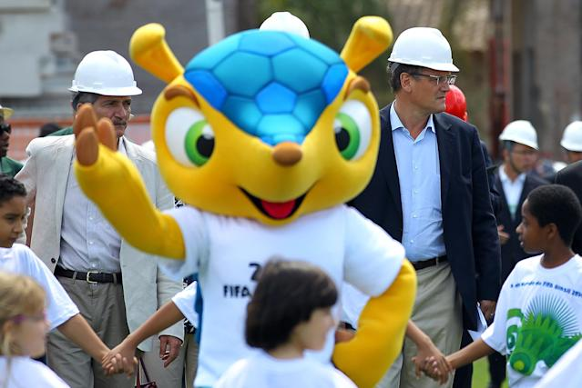 FIFA's secretary-general, Jerome Valcke (R) and Brazil's Minister of Sports, Aldo Rebelo (L) walk behind the armadillo, the mascot for the 2014 World Cup, during a visit to the Beira Rio stadium, in Porto Alegre, Brazil, on October 17, 2012. Less than two years before the 2014 World Cup kicks off in Brazil, half of the 12 host stadiums are at least 50 percent completed -- being renovation or construction. AFP PHOTO/Jefferson BERNARDESJEFFERSON BERNARDES/AFP/Getty Images