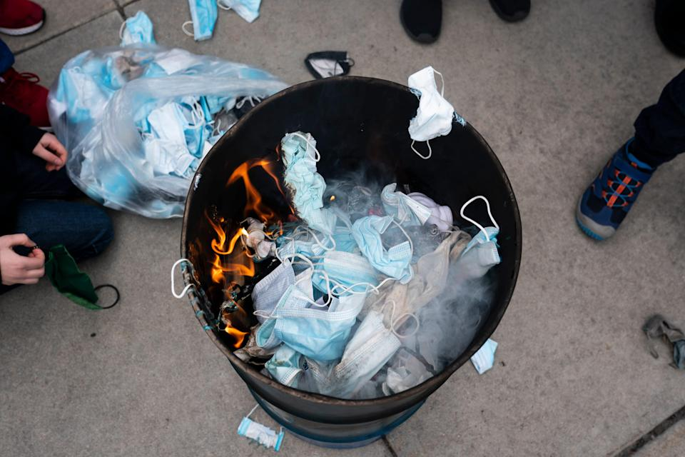 Attendees toss surgical masks into a fire during a mask burning event at the Idaho Statehouse on March 6, 2021 in Boise, Idaho.
