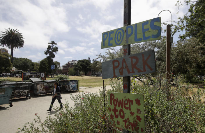 A woman walks behind a sign for People's Park in Berkeley, Calif., Thursday, July 18, 2019. Berkeley leaders voted unanimously this week to replace about 40 gender-specific words in the city code with gender-neutral terms. The effort to be more inclusive is drawing both praise and scorn. (AP Photo/Jeff Chiu)