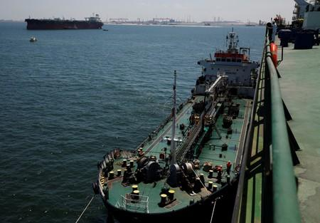 A bunker vessel supplies fuel to Hin Leong's Pu Tuo Shan VLCC supertanker in the waters off Jurong Island in Singapore