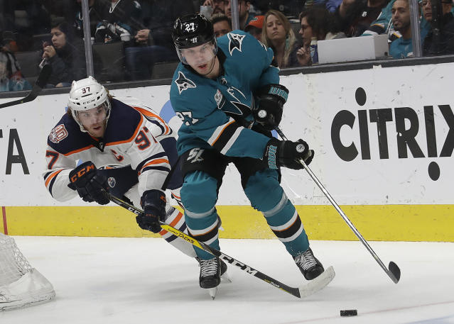 Edmonton Oilers center Connor McDavid, left, reaches for the puck next to San Jose Sharks right wing Joonas Donskoi (27), from Finland, during the second period of an NHL hockey game in San Jose, Calif., Tuesday, Jan. 8, 2019. (AP Photo/Jeff Chiu)