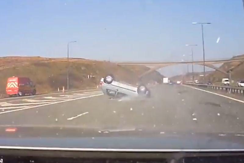 Dramatic: The footage shows the car skidding on its roof across the road (PA)