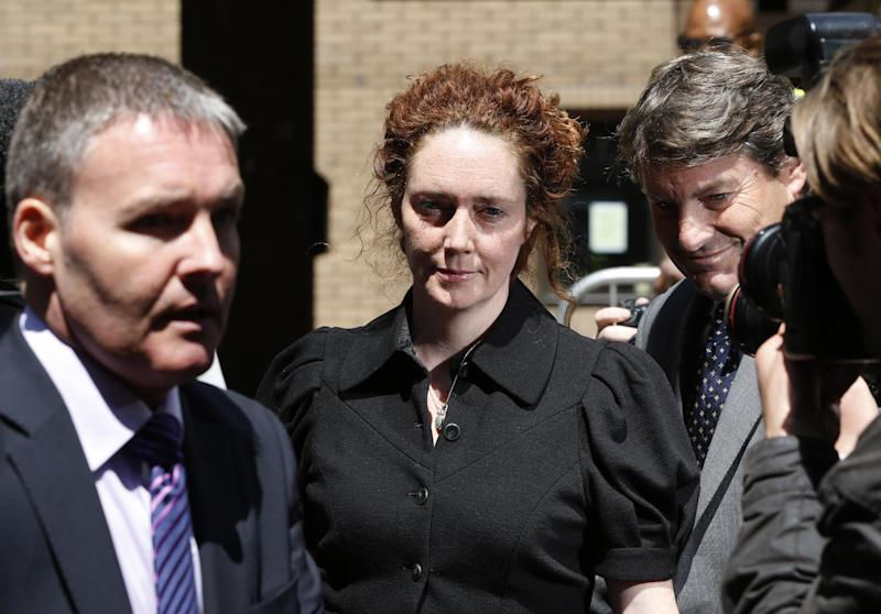 Former News International chief executive Rebekah Brooks, center, accompanied by her husband Charlie, right, leaves a court after entering a not guilty plea to charges related to phone hacking, in London, Wednesday, June 5, 2013. Brooks on Wednesday denied charges of phone hacking, bribing public officials and trying to thwart a police investigation into tabloid wrongdoing. (AP Photo/Lefteris Pitarakis)