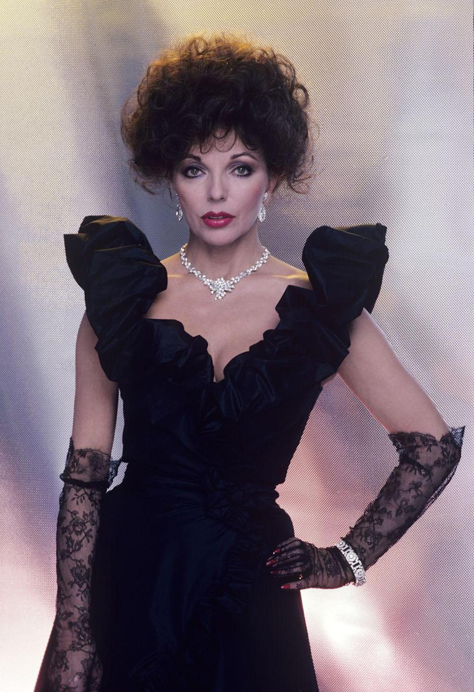 <p>Joan Collins wearing lace gloves, a ruffle-shoulder gown, and diamonds as Alexis Carrington in <em>Dynasty</em>. </p>