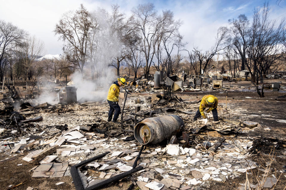 Firefighters Emiliano Saldivar, left, and Chris Martinez sift through debris to recover keepsakes for residents after the Mountain View Fire tore though the Walker community in Mono County, Calif., Wednesday, Nov. 18, 2020. (AP Photo/Noah Berger)