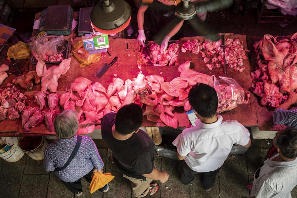 A customer picks out a pig ear at a pork stall inside the Dancun Market in Nanning, Guangxi province, China. Source: Getty