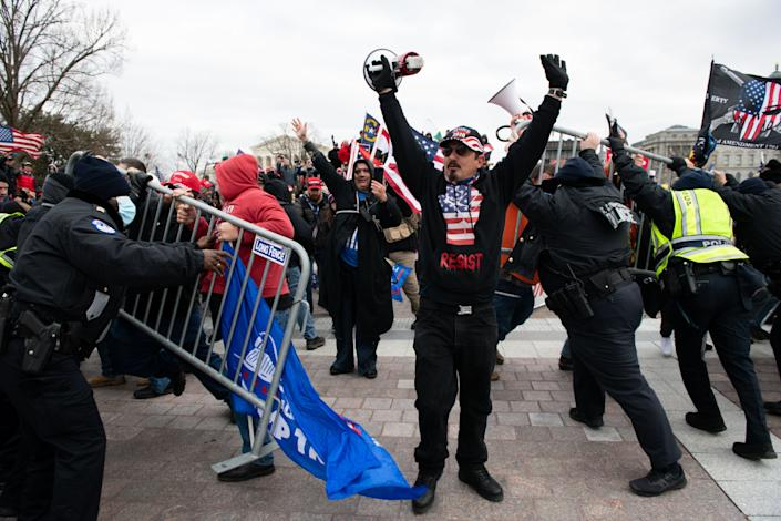 Demonstrators breach security fencing during a protest outside the U.S. Capitol in Washington, D.C., U.S., on Wednesday, Jan. 6, 2021. The House and Senate will meet in a joint session today to count the Electoral College votes to confirm President-elect Joe Biden's victory, but not before a sizable group of Republican lawmakers object to the counting of several states' electors. (Photo: Graeme Sloan/Bloomberg via Getty Images)